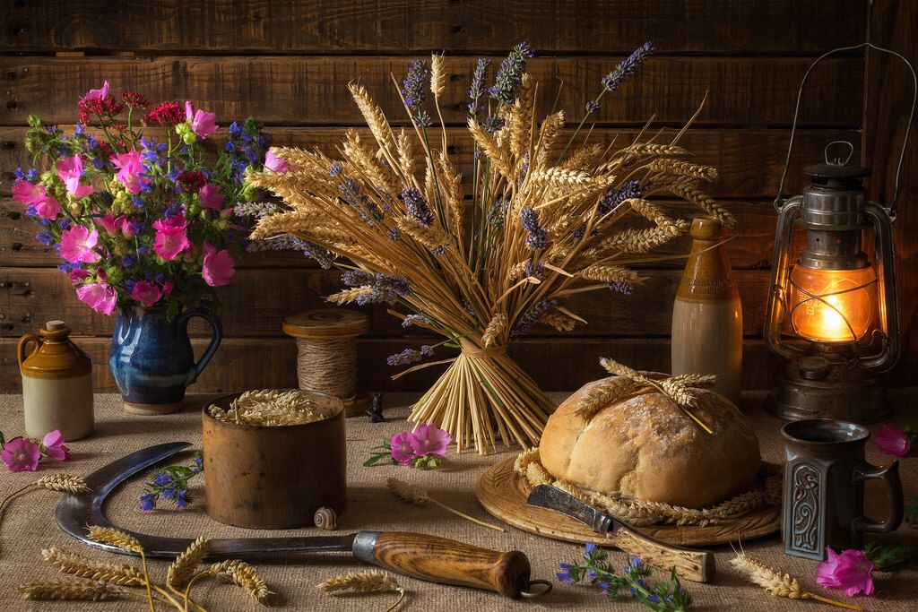 A harvest altar with bread, flowers, wine and sheaves